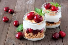 Cherry parfaits in mason jars over rustic wood. Healthy cherry parfaits in mason jars on a rustic wood background Royalty Free Stock Photography