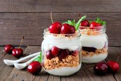 Cherry parfaits in mason jars, still life against rustic wood. Summer cherry parfaits in mason jars, still life against a rustic wood background Stock Images