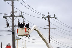 Cherry picker. Workers in cherry picker fixing power lines stock image