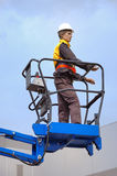 Cherry picker. Worker-mannequin in cherry picker over blue sky stock photos