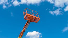 Cherry picker on blue sky background. Boom with lift bucket of heavy machinery. Orange platform of the telescopic construction lift in summer royalty free stock photo