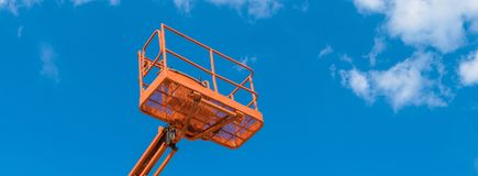 Cherry picker on blue sky background. Boom with lift bucket of heavy machinery. Platform of the telescopic construction lift close-up royalty free stock images