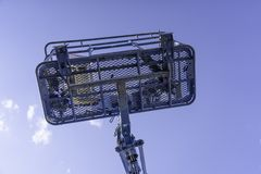 Cherry Picker Crane Underneath blue clear skies. From below royalty free stock photo