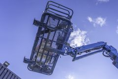 Cherry Picker Crane Underneath blue clear skies. From below stock image