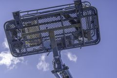 Cherry Picker Crane Underneath blue clear skies. From below royalty free stock images