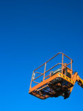 Cherry Picker Machine. Empty orange-coloured bucket of a cherry picker machine against a blue sky royalty free stock images