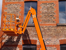 Cherry picker. Orange coloured cherry picker next to old factory or warehouse building royalty free stock image