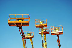 Cherry Pickers. Mechanical platform hoist 'cherry pickers' against a blue sky stock photo