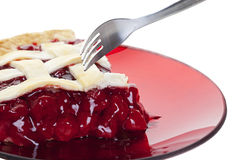 Cherry Pie. A serving of cherry pie about to be cut into with a fork. Shot on white background stock photography