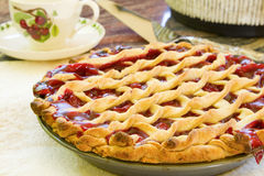 Cherry Pie. Homemade cherry pie cooling on a table with a tea cup in the background royalty free stock image