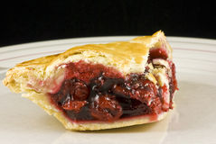 Cherry Pie. Large slice of cherry pie captured on a plate with a black background stock photo