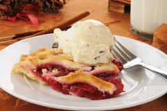 Cherry pie ala mode. A slice of hot cherry pie with a scoop of chocolate chip ice cream royalty free stock photos