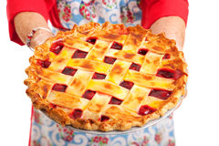 Cherry Pie Closeup. Closeup of a homemade cherry pie being held by a stereotypical grandma. on white royalty free stock photos