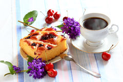 Cherry pie and cup of tea. Cherry pie decorated with flowers with a cup of tea on the table Royalty Free Stock Photo