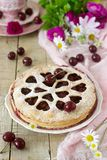 A cherry pie decorated with heart-shaped ornamentation with a cup of tea, a bouquet of flowers and ripe cherry berries. stock photos