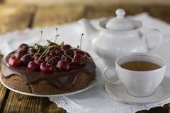 A cherry pie, with fresh cherries a cup of tea and a kettle royalty free stock image