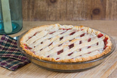 Cherry pie. Fresh homemade cherry pie sitting in a rustic setting Royalty Free Stock Photo
