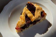 Cherry pie in harsh light. In white plate stock photos