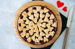 Cherry pie with heart shape decorations from flaky dough on a wh. Ite backdrop Royalty Free Stock Photo