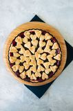 Cherry pie with heart shape decorations from flaky dough on a wh. Ite backdrop Stock Image