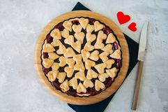 Cherry pie with heart shape decorations from flaky dough on a wh. Ite backdrop Royalty Free Stock Photography