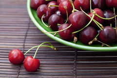 Cherry in plate on a bamboo mat Royalty Free Stock Photo