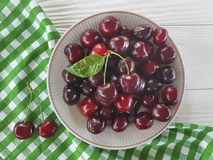 Cherry raw in a plate summer dessert organic natural delicious ripe on a white wooden. Cherry in a plate a white wooden raw delicious summer ripe organic natural stock image