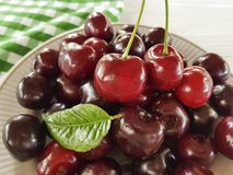 Cherry raw in a plate summer dessert health meal heap organic natural delicious ripe on a white wooden. Cherry in a plate a white wooden raw delicious summer royalty free stock images