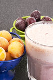 Cherry and plum in a colander and a milkshake Stock Photography