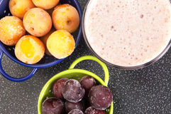 Cherry and plum in a colander and a milkshake Stock Photo