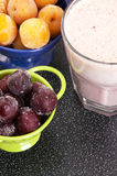 Cherry and plum in a colander and a milkshake Stock Photos