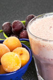 Cherry and plum in a colander and a milkshake Stock Images