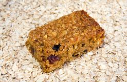 Cherry and raisin flapjack on an oat background. A piece of chewy cherry and raisin flapjack on a background of jumbo oats Royalty Free Stock Photography
