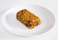 Cherry and raisin flapjack on a white plate. A piece of cherry and raisin flapjack on a white plate on a white tablecloth Stock Photography