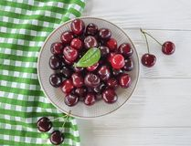 Cherry raw in a plate summer dessert meal heap organic natural delicious ripe on a white wooden. Cherry in a plate a white wooden raw delicious summer ripe royalty free stock images