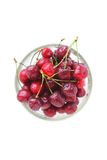 Cherry red with drops in a glass bowl on a white background Stock Image