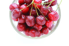 Cherry red with drops in a glass bowl on a white background Royalty Free Stock Photos