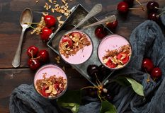 Cherry smoothie. In a glass topped with fresh cherries and granola Stock Images