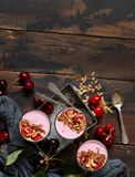 Cherry smoothie in a glass. Topped with fresh cherries and granola Royalty Free Stock Images
