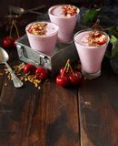 Cherry smoothie. In a glass topped with fresh cherries and granola Royalty Free Stock Photos