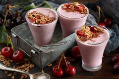 Cherry smoothie in a glass. Topped with fresh cherries and granola Stock Photography