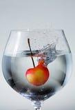 Cherry Splash. Single cherry making a splash as it falls into a glass of water Royalty Free Stock Photo