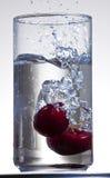 Cherry Splash in Water. An image of fresh cherries splashing into glass of fresh water Stock Photo