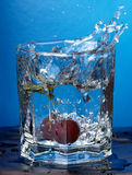 Cherry splashed into water. Cherry in a water glass on a dark blue background Stock Photos