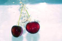Cherry splashing Stock Images