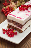 Cherry sponge cake with cream and red currant. Wooden background. Top view. Close-up Royalty Free Stock Image