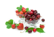 Cherry and strawberry in glass bowls on white background Stock Photography
