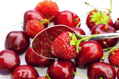 Cherry and strawberry in a spoon Stock Images