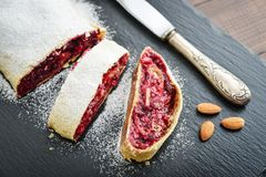 Cherry strudel with almond. And powdered sugar on black slate background Stock Photos