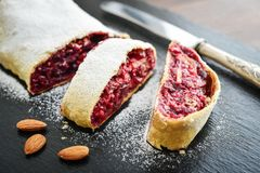 Cherry strudel with almond. And powdered sugar on black slate background Royalty Free Stock Images